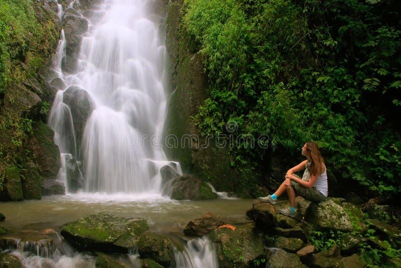 Sammanträde för den unga kvinnan på Simangande faller på den Samosir ön, Sumat royaltyfri fotografi