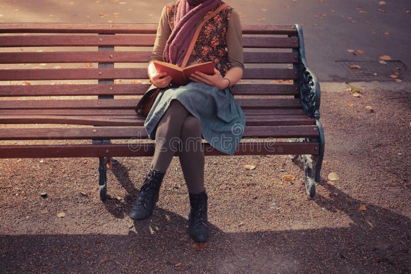 Sammanträde för den unga kvinnan parkerar på bänken med boken arkivbild