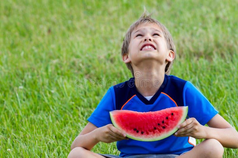 Sammanträde för det lilla barnet på grönt gräs parkerar in och äta vattenmelon royaltyfria foton