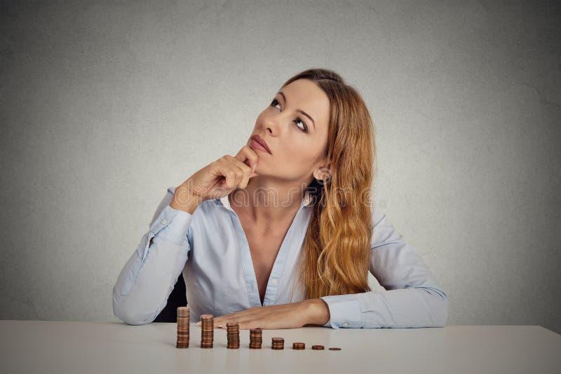 Sammanträde för företags ledare för affärskvinna på tabellen med den växande bunten av mynt arkivfoton