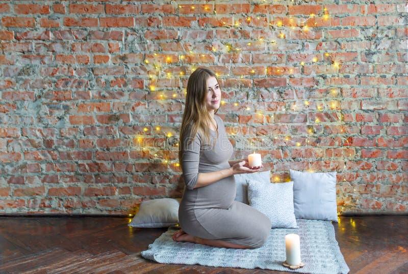 Sammanträde för förväntansfull moder på golvet och innehavet per stearinljuset arkivbilder