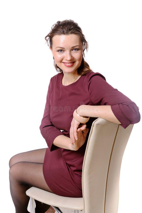 Sammanträde för formell klänning för flicka iklätt på en stol och le royaltyfria foton