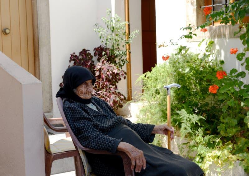 Sammanträde för gammal kvinna i hennes trädgård, Sisi, Kreta arkivbilder