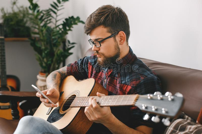 Sammanträde för gitarr för ung gitarristhipster som hemmastatt hållande bläddrar smartphonen som kontrollerar massmedia arkivbild