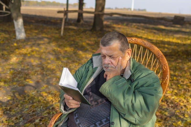 Sammanträde för hög man i vide- stol och läs- dagbok royaltyfri bild