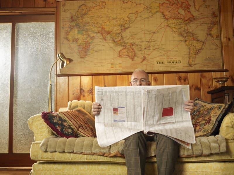 Sammanträde för hög man på Sofa Reading Newspaper arkivbilder