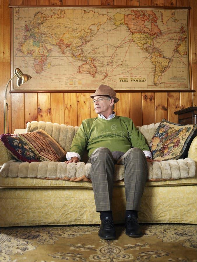 Sammanträde för hög man på soffan arkivfoto