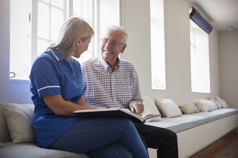Sammanträde för hög man som ser fotoalbumet med omsorgsjuksköterskan royaltyfria bilder