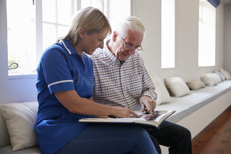 Sammanträde för hög man som ser fotoalbumet med omsorgsjuksköterskan arkivfoton