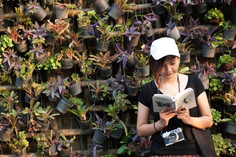 Sammanträde för Hipsterkvinnatonåringen tycker om läseboken på pir Läsebokbegrepp för ung kvinna, tonat retro filter royaltyfri foto
