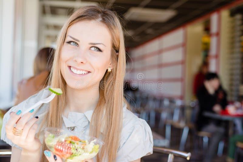 Sammanträde för kvinna för Closeupstående gladlynt härligt blont i coffee shop som rymmer lyckligt le för läcker sallad i restaur arkivfoto