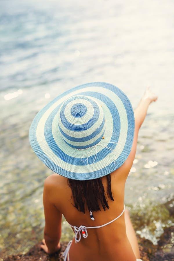 Sammanträde för kvinna för sommarsemester på stranden som ser havet arkivfoto