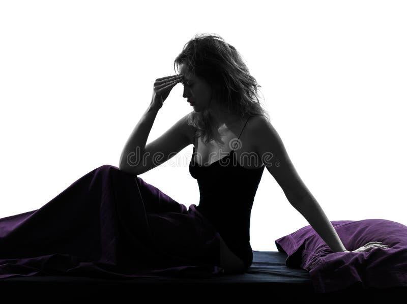 Sammanträde för kvinnahuvudvärkhagover på sängkontur royaltyfri bild