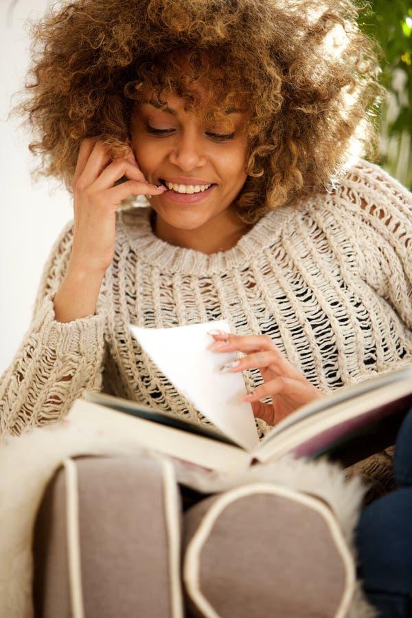Sammanträde för kvinnlig student för afrikansk amerikan hemma och läsebok arkivbild