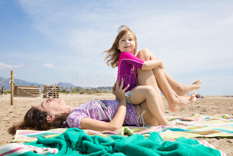 Sammanträde för litet barn på kvinnan som rymmer henne ben på stranden royaltyfri foto