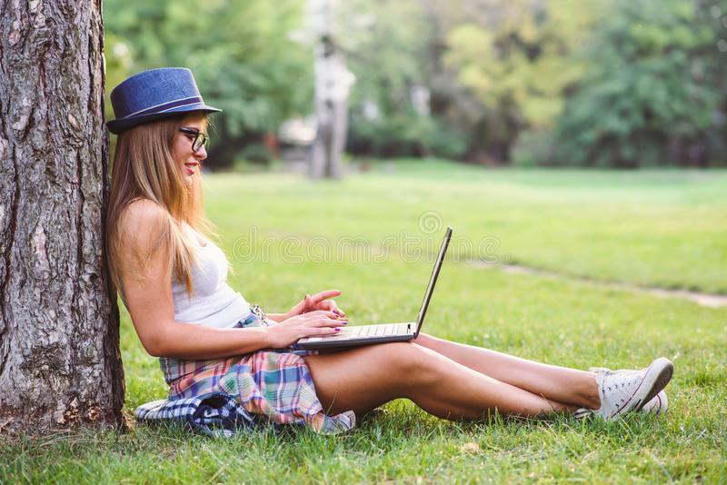 Sammanträde för student för ung kvinna på gräs som arbetar på bärbar datordatoren arkivbilder