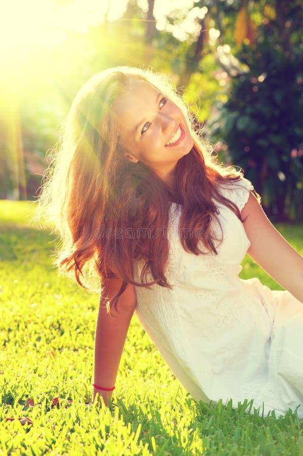 Sammanträde för tonårs- flicka för skönhet romantiskt på grönt gräs royaltyfria foton