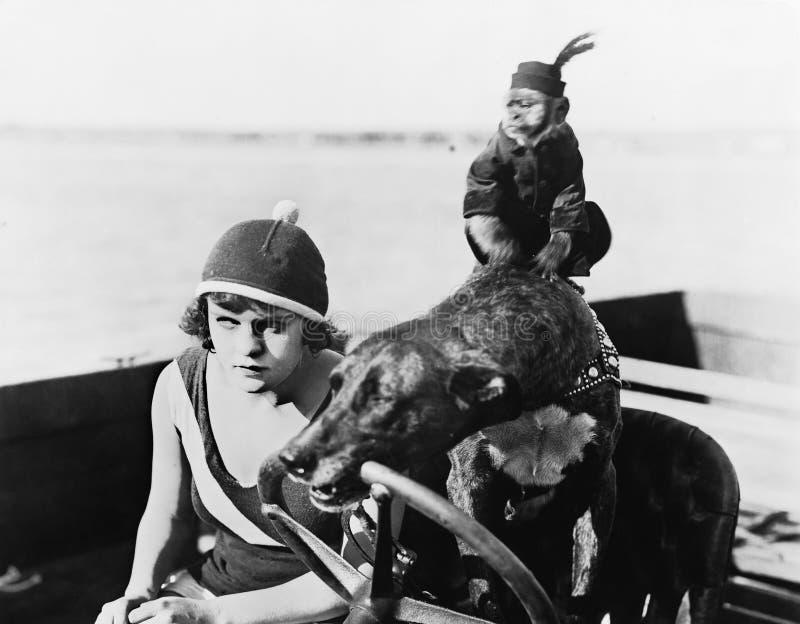 Sammanträde för tonårs- flicka i en motorbåt som är drivande vid en hund (alla visade personer inte är längre uppehälle, och inge arkivfoto