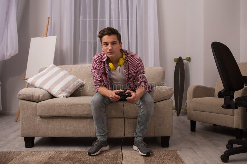 Sammanträde för tonårs- pojke på soffan som spelar dataspelar arkivfoton