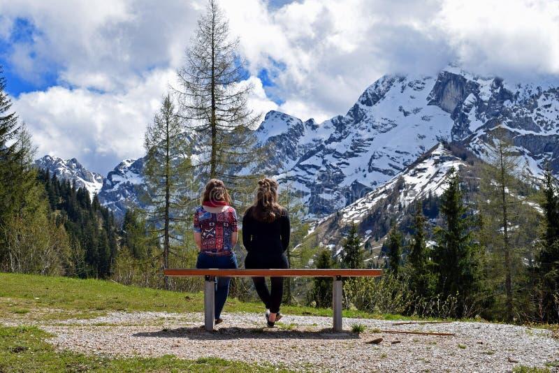 Sammanträde för två kvinna på bänk och hållande ögonen på härlig bergsikt av tyska fjällängar royaltyfri fotografi