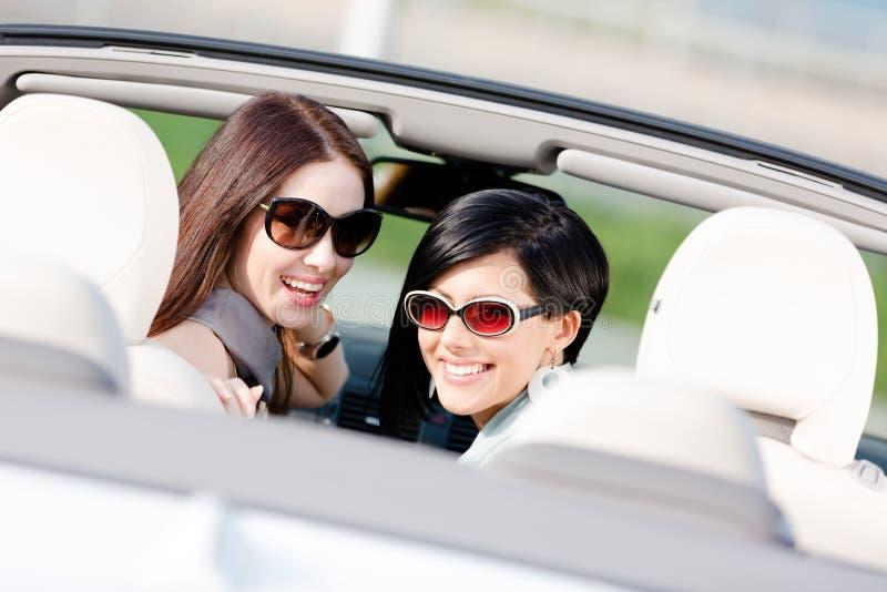 Sammanträde för två lyckligt flickor i bilen royaltyfria bilder