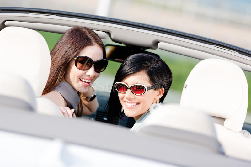 Sammanträde för två lyckligt flickor i bilen royaltyfri foto