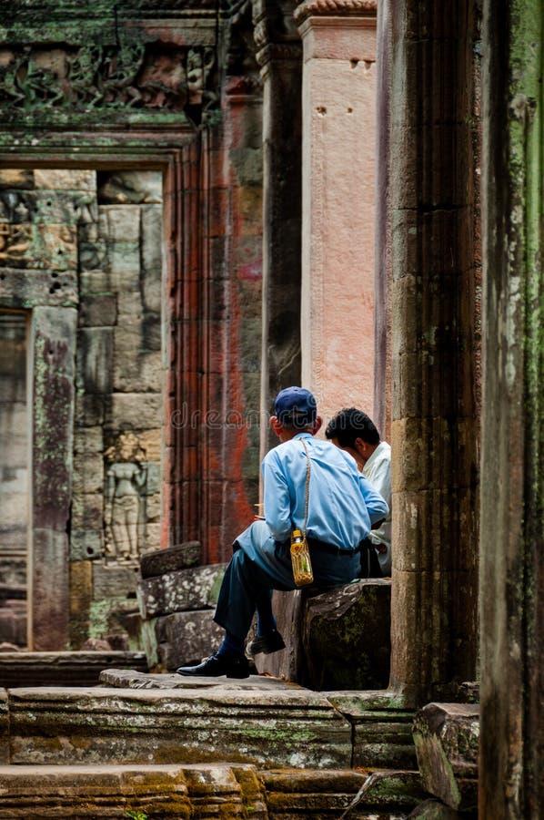 Sammanträde för två man mellan stendörrar arkivfoton