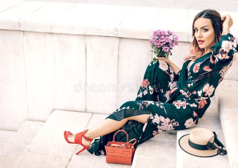 Sammanträde för ung dam på trappa med blommor royaltyfri foto
