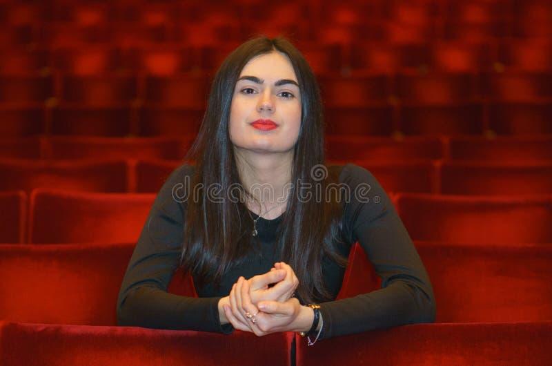 Sammanträde för ung kvinna för brunett i den tomma röda teaterkorridoren arkivfoto