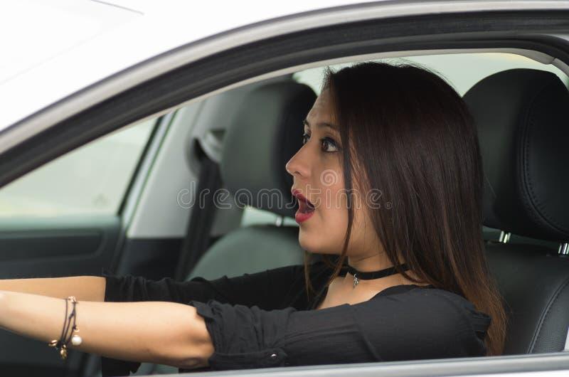 Sammanträde för ung kvinna för Closeup, i bilkörning med växelverkan som utifrån förvånas, som sett chaufförfönster, kvinnlig royaltyfri fotografi