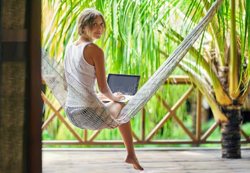 Sammanträde för ung kvinna i en hängmatta med bärbara datorn i en tropisk resor royaltyfri foto