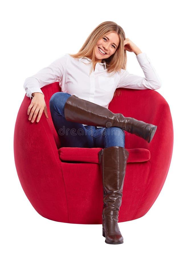 Sammanträde för ung kvinna i en röd stol arkivbild