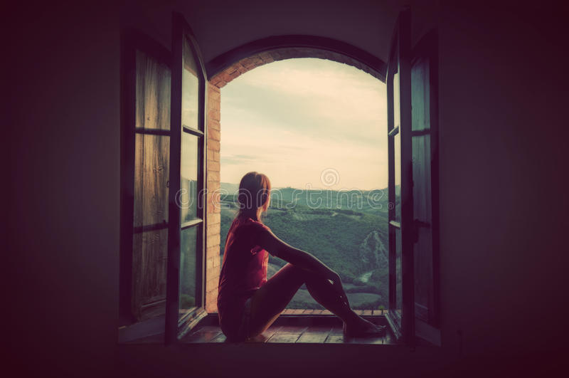 Sammanträde för ung kvinna i ett öppet gammalt fönster som ser på landskapet av Tuscany, Italien royaltyfria bilder