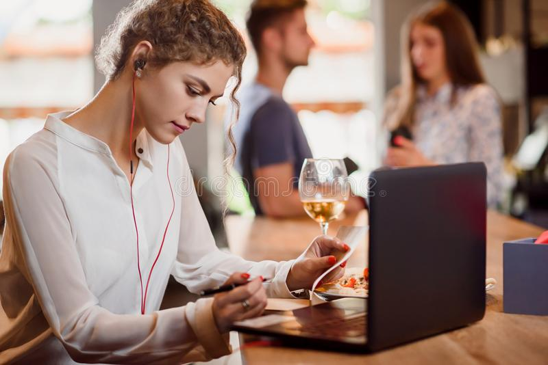 Sammanträde för ung kvinna i kafé och arbete med anteckningsboken royaltyfri fotografi