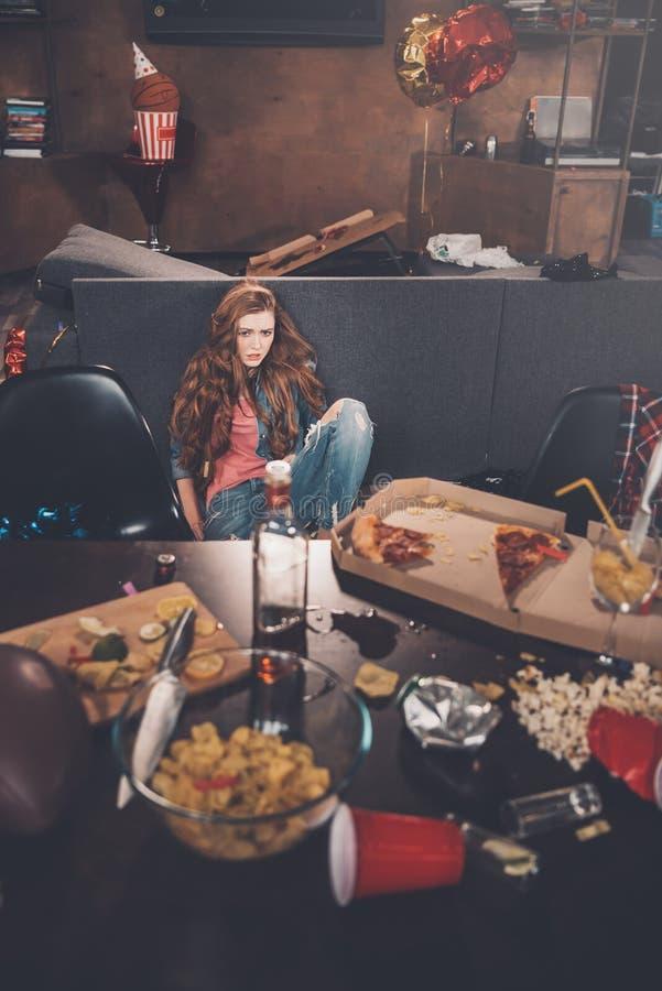 Sammanträde för ung kvinna i smutsigt rum efter parti royaltyfri fotografi