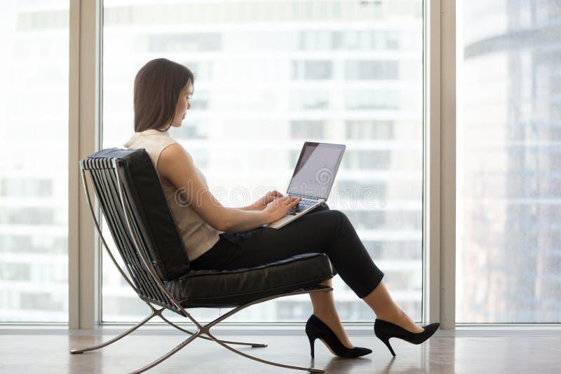 Sammanträde för ung kvinna i stol som använder bärbara datorn för att studera direktanslutet royaltyfri fotografi