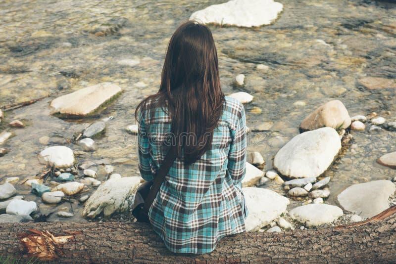Sammanträde för ung kvinna längs floden royaltyfri bild