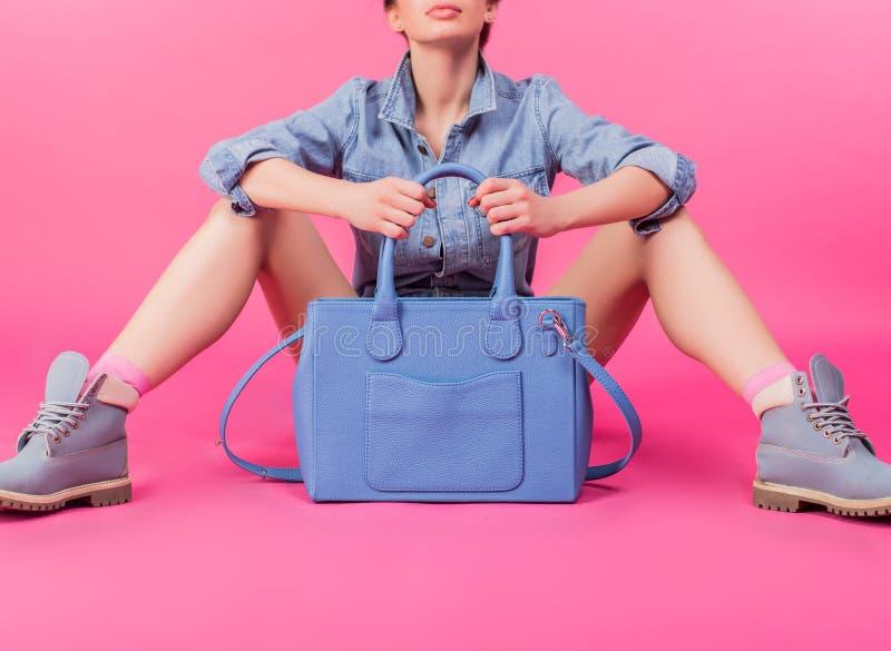 Sammanträde för ung kvinna och hållande lyxig handväska royaltyfri bild