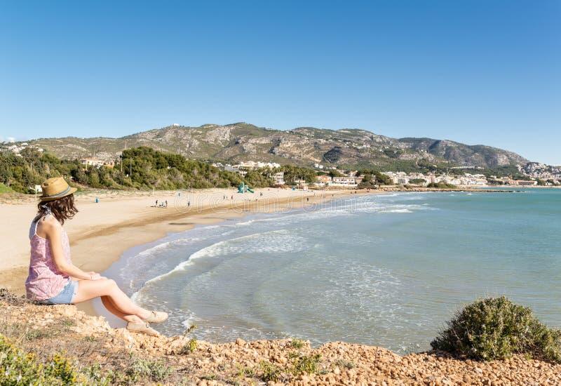 Sammanträde för ung kvinna och se en panoramautsikt av en sandig strand på den medelhavs- kusten arkivbild