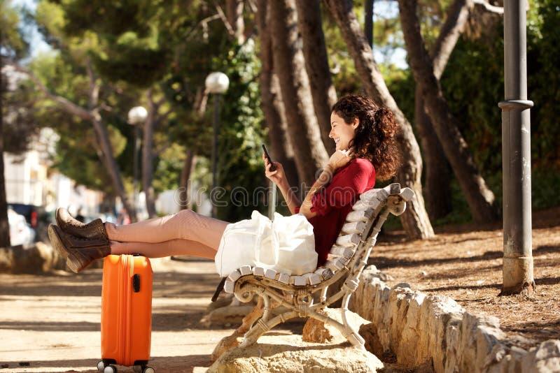 Sammanträde för ung kvinna på bänk med resväskan och se mobiltelefonen royaltyfria bilder