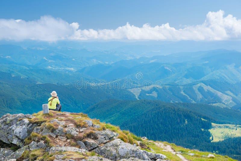 Sammanträde för ung kvinna på bergklippan royaltyfri foto