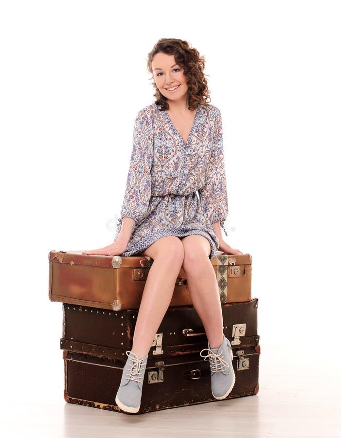 sammanträde för ung kvinna på bunt av resväskor fotografering för bildbyråer