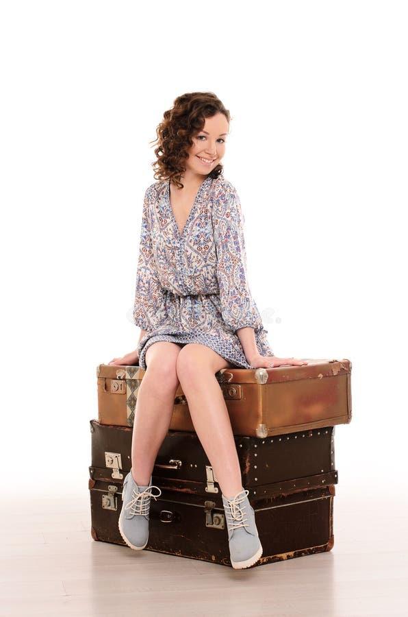 sammanträde för ung kvinna på bunt av resväskor royaltyfri bild
