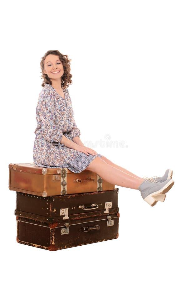 sammanträde för ung kvinna på bunt av resväskor arkivbild