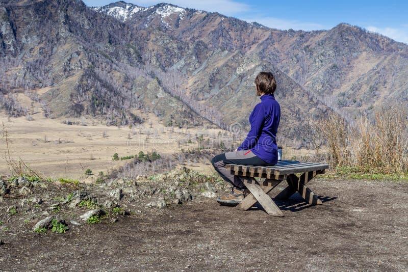 Sammanträde för ung kvinna på en bänk och se berg med med en kopp te royaltyfria foton