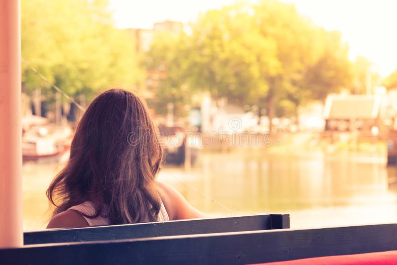 Sammanträde för ung kvinna på en bänk som håller ögonen på skeppsdockan av fjärden på s arkivbilder