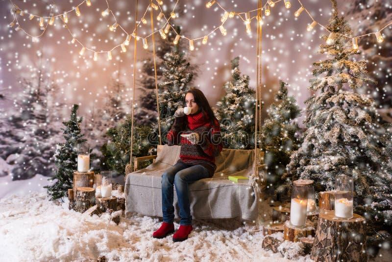 Sammanträde för ung kvinna på en gunga med en filt under flashligen arkivfoto