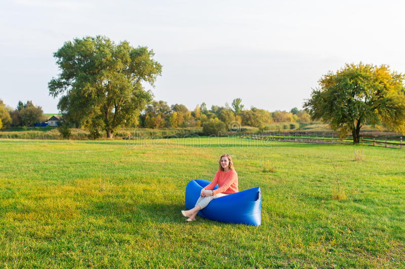 Sammanträde för ung kvinna på en luftsoffa mot bakgrunden av den gröna ängen arkivfoton