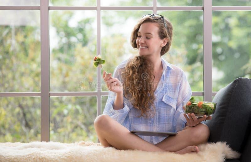 Sammanträde för ung kvinna på en soffa genom att använda minnestavlan och innehavet en salladbunke royaltyfri fotografi
