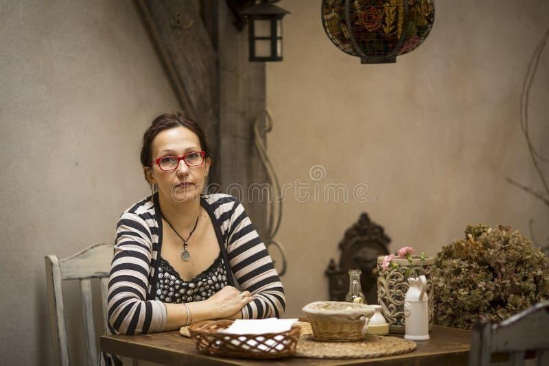 Sammanträde för ung kvinna på en tabell i det gamla kafét tryst arkivbilder